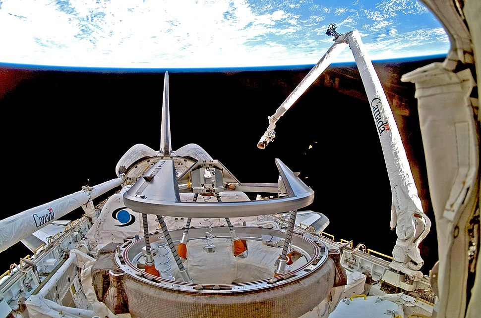 """A shuttle in space, with Earth in the background. A mechanical arm labelled """"Canada"""" rises from the shuttle."""