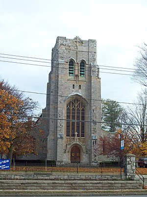 A stone church tower with a level top, gently arched pointed windows and a small wooden door in the base. In front of it are telephone lines and a set of steps.