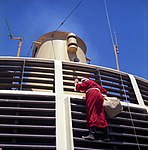 Santa Claus climbing the grill in front of the forward funnel above the Bridge on Oriana (5074435121).jpg