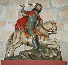 This crudely carved statue shows St James as a bearded knight in armour with a red cloak and upraised sword. He rides a white galloping horse which is trampling the bodies of two armoured men.