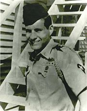 Head and torso of a smiling young man standing in front of a wooden staircase, wearing a short-sleeved military shirt with shoulder cords and a garrison cap.