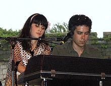 Deschanel and M. Ward performing as She & Him on a Wurlitzer electric piano at the Newport Folk Festival on August 2, 2008