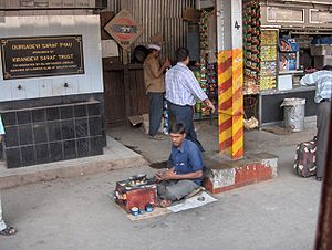 Shoeshiner - A boot polisher on a railway platform in Mumbai, India.