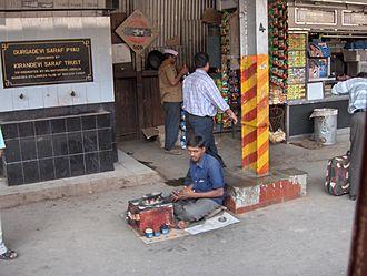 Shoeshiner - A boot polisher on a railway platform in Mumbai, India.