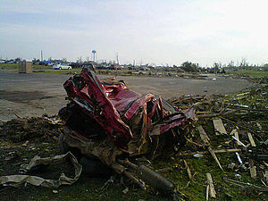 2011 Smithville, Mississippi tornado - The remains of an SUV that was thrown half a mile into the top of the water tower seen in the background before bouncing off, traveling another 1/4 mile though the air, impacting the ground and eventually coming to rest in the parking lot of the E.E. Pickle funeral home on the opposite side of town.