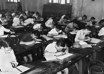 English: School children doing exams inside a ...