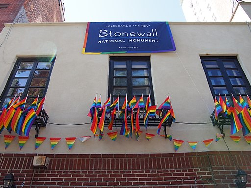 "A two-storey building with a brick first floor and a white-ish/tan concrete upper floor. The image focuses on the upper floor where the windows are bedecked with many rainbow flags and rainbow flag bunting. A blue banner with rainbow edging hangs down from the roof with the words ""Celebrating the Stonewall National Monument."""