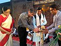 "Sudarshan Bhagat lighting the lamp at ""Aadi Mahotsav"" a Mega fortnight long National Tribal festival with the theme A celebration of the spirit of Tribal culture, cuisine & commerce, at Central Park, Rajiv Chowk, New Delhi.jpg"