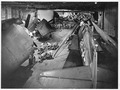 Surrounded by F6F's ordnance men work on bombs on hangar deck of USS Yorktown (CV-10). Officers and men in background... - NARA - 520771.tif