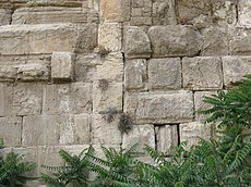 Large stones in a wall with a straight joint running vertically between masonry of two distinctive types