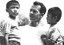 Black and white photograph of Tom Dooley. A white adult man holding two children of Asian descent in his arms.