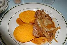 Round, yellow cakes topped with fried meat and onions.