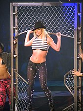 A blond female performer. She is standing inside a moving jungle gym-like metal structure, she is being carried by two people, who are halfway out of the picture. Her hands are grabbing the structure, she is looking to the left side of the picture. She is wearing a black hat leaning down to the left, a striped top exposing her midriff and sparkly black pants.