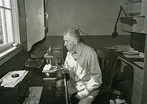 Trevor Kincaid - Trevor Kincaid at a workbench with a microscope, c. 1950