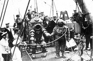 Monochrome view of the deck of a ship with a pair of divers, and a group of onlookers, some of which are crew of the ship. To the left is a diver in an armoured suit, and to the right the diver is in standard diving dress with copper helmet