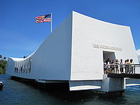 White Arizona memorial with downward sloped top and American flag
