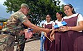 US Navy 070731-N-6081J-034 A Salvadoran soldier passes out American and Salvadoran flags at a municipal park in Acajutla, as part of a ceremony celebrating the humanitarian contributions of the hospital ship USNS Comfort (T-AH.jpg