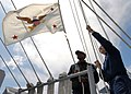 US Navy 070815-N-9898L-005 Quartermaster Seaman Lamont Sports (left) and Quartermaster 3rd Class Richard Nute raise the flag of the General Counsel for the Department of Defense, the Honorable William J. Haynes II.jpg