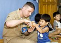 US Navy 070825-N-0483B-002 Senior Chief Cryptologic Technician (Technical) Robert Stewart, 7th Fleet staff member embarked aboard amphibious command ship USS Blue Ridge (LCC 19), colors with a child of the Aehyang Children's We.jpg