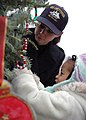 US Navy 071207-N-0167W-001 Airman Apprentice Tenika Michaels assigned to USS Constitution helps a preschooler decorate the ship's Christmas tree.jpg