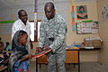 US Navy 071215-N-3931M-098 U.S. Army Sgt. 1st Class Calvin Coliston from Combined Joint Task Force-Horn of Africa (CJTF-HOA) presents a gift to a local student at a school dedication ceremony in Ali Adde.jpg