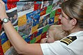 US Navy 080725-N-7138C-015 Lt. Cmdr. Jeannie Groeneveld shows her son a quilt made from family photos given to her by the Armed Services YMCA.jpg