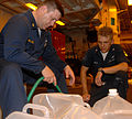US Navy 080912-N-7544A-024 Chief Gunner's Mate William Walker and Aviation Ordnanceman 3rd Class Chris West, both embarked aboard the amphibious assault ship USS Kearsarge (LHD3) fill two-and-a-half gallon water containers.jpg