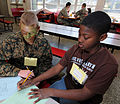 US Navy 090221-N-5328N-140 Saturday Scholar Mentor Pfc. Mathew Alexander, from Hendersonville, N.C., plays tick-tack-toe with a West Pensacola Elementary School Saturday Scholar student.jpg