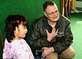 US Navy 090228-N-8546R-003 Cmdr. Keith Harris, assistant reactor officer for the aircraft carrier USS George Washington (CVN 73), introduces himself to children at Kobo Cottage during a community relations project.jpg