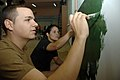 US Navy 090707-A-8397T-002 Seaman Wesley Graham assigned to Beachmasters Unit TWO and Ensign Vanessa Nieves assigned to amphibious dock landing USS Oak Hill (LSD 51) paint a wall inside Hospital Hogar Pineyro in Montevideo, Uru.jpg