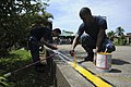 US Navy 100920-N-9964S-048 Quartermaster 2nd Class Shawn Dekle and Fireman Christopher Thomas paint a yellow line on a basketball court during a co.jpg