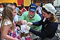 US Navy 110626-N-WE887-054 Jennifer Marland helps Brian Coval make a mob hat for his daughter's American Girl doll during the 3rd annual Girls Make.jpg