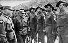 Soldiers wearing slouch hats lined up on parade as a reviewing officer conducts an inspection