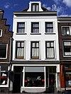 foto van Pand bestaande uit drie bouwlagen en een kap loodrecht op de straat