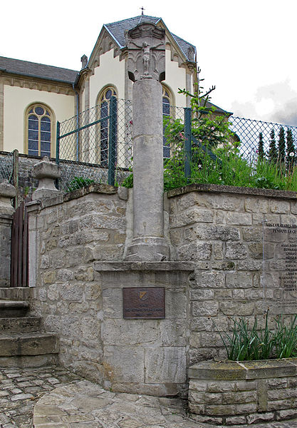 Wayside cross in Hobscheid, Luxembourg, ahead of the church