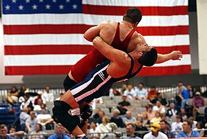Two U.S. Air Force members wrestling in a Grec...