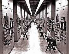 A long corridor with many consoles with dials and switches, attended by women seated on high stools.