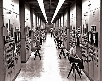Timeline of the Manhattan Project - Operators at their calutron control panels at Y-12. Gladys Owens, the woman seated in the foreground, did not know what she had been involved with until seeing this photo in a public tour of the facility fifty years later.