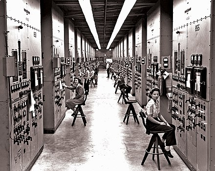 Operators at their calutron control panels at Y-12. Gladys Owens, the woman seated in the foreground, did not know what she had been involved with until seeing this photo in a public tour of the facility fifty years later. Y12 Calutron Operators.jpg