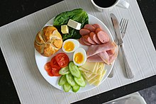 Plate of veggies, bread, meats, cheese, and a sliced, soft boiled egg.
