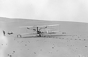 Wright Flyer III - The Wright Flyer III in its two-seat configuration at the Kill Devil Hills, May 1908. Take-offs were made from the monorail launch track; the catapult and derrick were not used. This is the only surviving Wright brothers photo of the airplane in this configuration. A news photographer took a picture of the aircraft in flight from a distance, but very few details are visible.