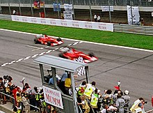 Photograph sowing Rubens Barrichello making way to allow Michael Schumacher to cross the finish line ahead of him