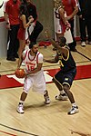 A basketball player in a dark blue uniform is defending against a player in a white uniform.