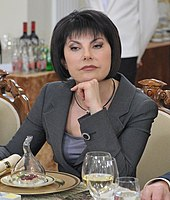 A woman with black hair, Tatyana Mitkova, sitting at a table