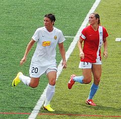 Wambach in a white uniform surrounded by a defender in a red uniform.