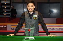 Ding smiling at the camera stands behind a snooker table with his German Masters Trophy.
