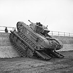 A Churchill tank of 79th Armoured Division uses a Churchill Ark to scale a sea wall during trials near Saxmundham, 11 March 1944. H36593.jpg