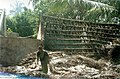 A lady arranges coconut leaves to build a new hut in Pulianchavadi near Pondicherry.jpg