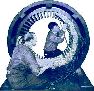 Blue-tinted photograph of two men working on a large circular piece of electrical equipment.