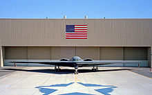 Front view of tailless aircraft parked in front of building. On the building face is a blue and red rectangular flag. A star-shaped artwork is on taxiway in front of aircraft.